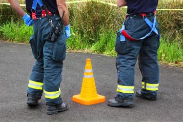hasiči stoja pri kuželi